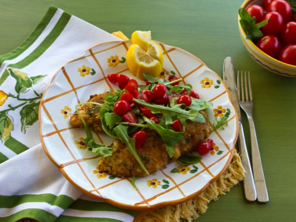 Crispy, golden brown chicken cutlets, ripe cherry tomatoes, and peppery arugula