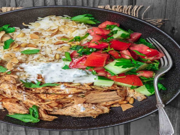 These dinner bowls are a modern twist on the beloved Lebanese chicken fatteh casserole. Lebanese-spiced poached chicken with toasted pita and mint yogurt sauce, served in dinner bowls with Lebanese rice and Mediterranean salad.